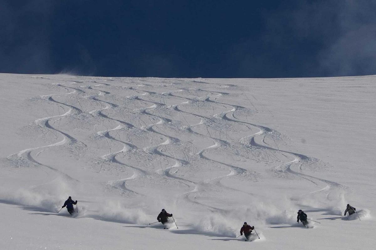 Northern Escape Heliskiing - Spuren von 5 Skifahrern im Pulverschnee