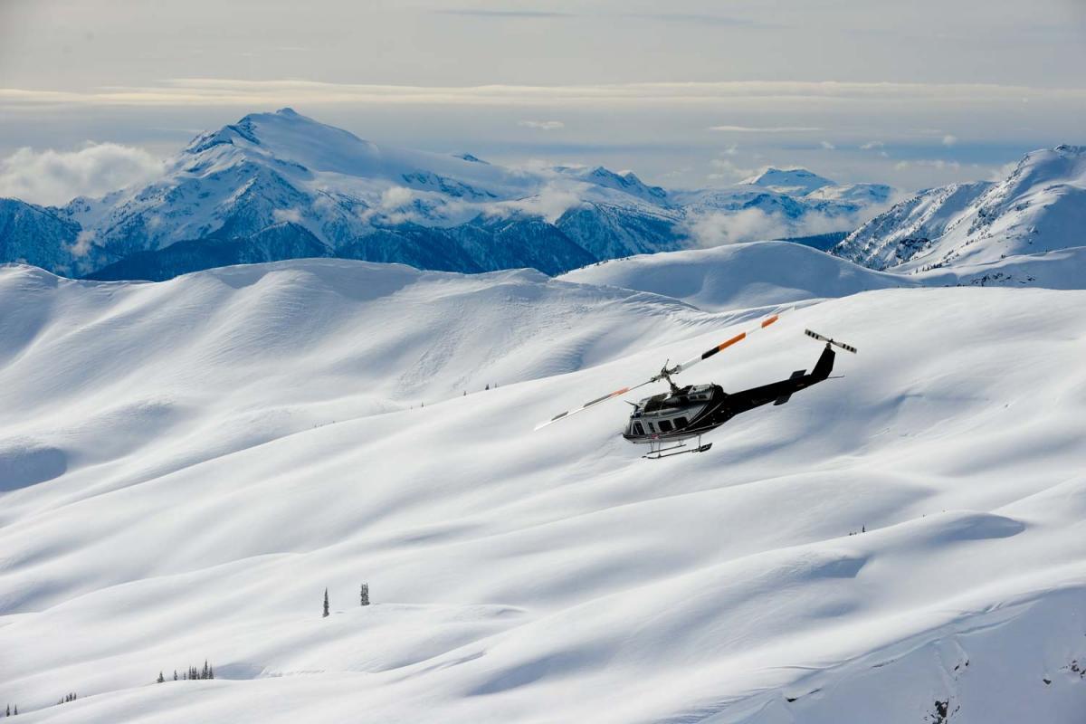 Helikopter über schneededeckten Bergen von Selkirk Tangiers Heliskiing