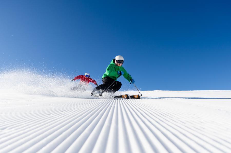 2 Skifahrer auf frisch gewalzten Pisten
