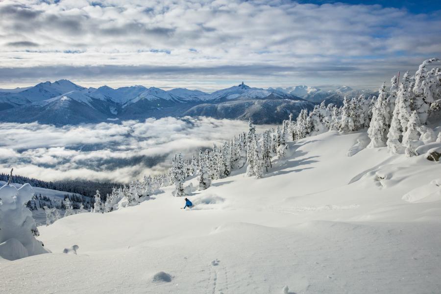 Skifahrer im Pulverschnee in Whistler mit Bergen im Hintergrund