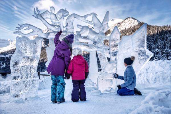 Eine familie schaut sich Eisskulpturen in Lake Louise an