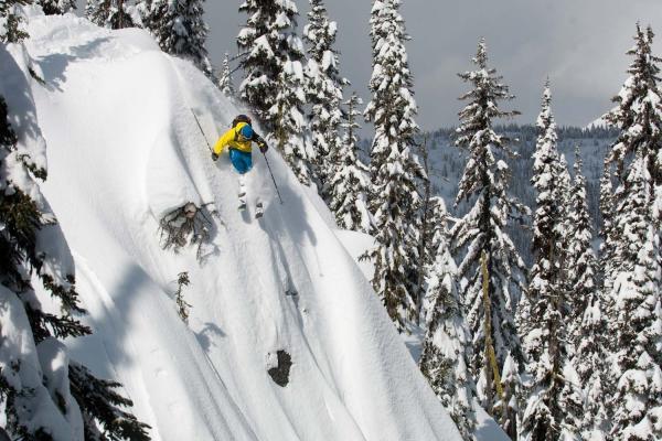 Skifahrer im Pulverschnee fährt steilen Abhang hinunter