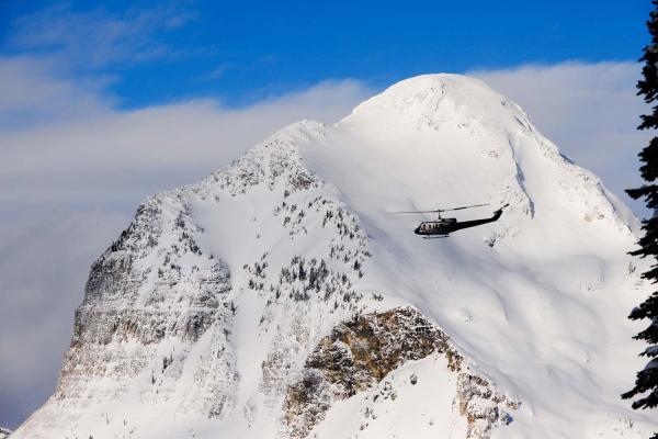 Helikopter von Selkirk Tangiers Heliskiing vor schneededeckten Bergen