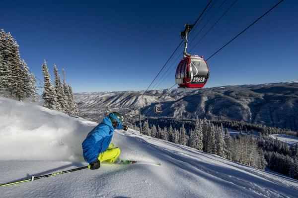 Skifahrer fährt im Pulverschnee unterhalb Ski-Gondel mit Schriftzug Aspen