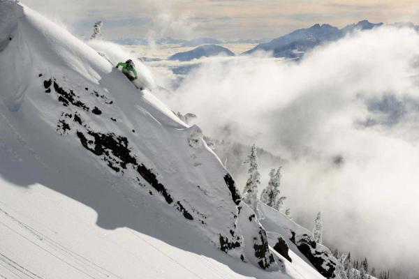 Skifahrer in grüner Jacke fährt ski im Backcountry